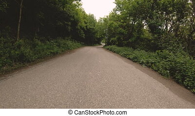 Running on an asphalt road in the forest is a first-person...