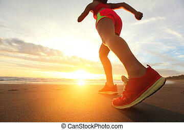 Running - Woman Runner feet running on the beach at sunrise...