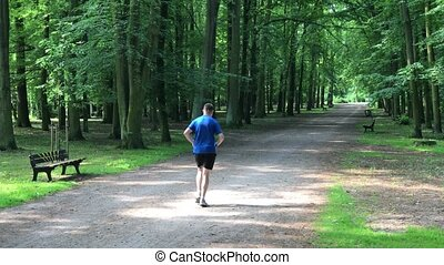 Running round the path - Young man running in the morning in...