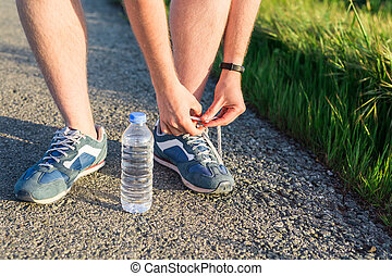 Running shoes. Barefoot running shoes close up. male athlete tying laces for jogging on road. Runner ties getting ready for training. Sport lifestyle.