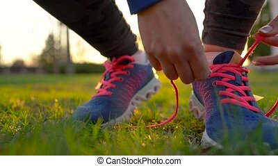 Running shoes - woman tying shoe laces. Slow motion
