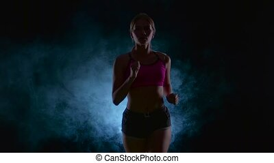 Running sport girl. Front view. Black screen in the smoke. Silhouette. Slow motion. Close up