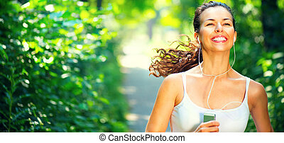 Running sporty girl. Beauty young woman with earphones jogging in the park
