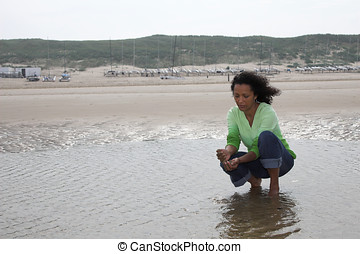 Running the sand through her fingers - Pretty black woman ...