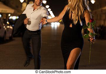 Running through a city - An elegant couple holding hands ...