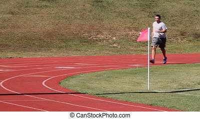 Overweight adult man runs a sports track for exercise and fitness to burn calories and lose weight.