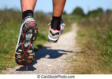 Trail running. Freeze action closeup of running shoes in action. Shallow depth of field, focus on left shoe.