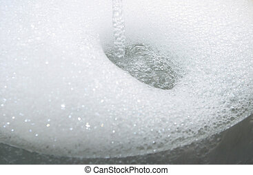 soap suds - Running water causes soap suds in a cooking pot.