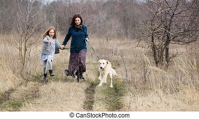Running with cute dog in nature - Mother and daughter ...