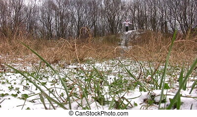 Running woman. Grass under snow.