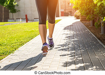 Running woman in black sports outfit (half body photo) on the sidewalk