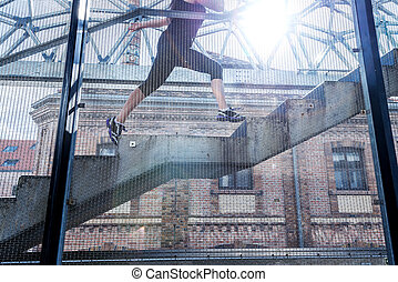 Running woman in black sports outfit, running up the stairs ,detail photo