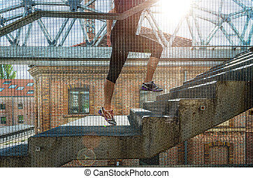 Running woman in black sports outfit, running up the stairs