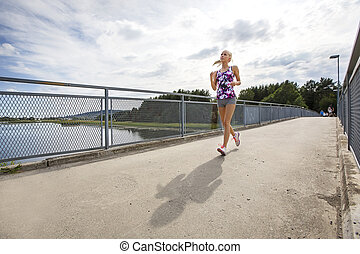 Running woman jogs in sunshine outdoor on bridge
