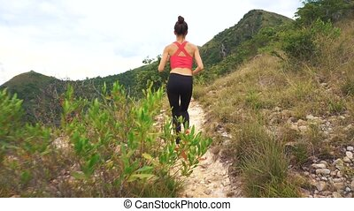 Running woman on mountain road. Sport fitness girl exercising outside in mountains living healthy lifestyle enjoying outdoor activity.
