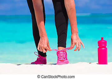 Running woman tying running shoe laces while run on white...