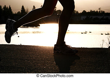 Running woman - Woman jogging along a river at sunset