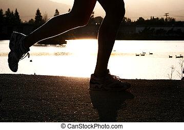 Running woman - Woman jogging along a river at sunset