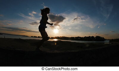 Running young woman in park at sunset, slow-motion, hands in a fist, silhouette