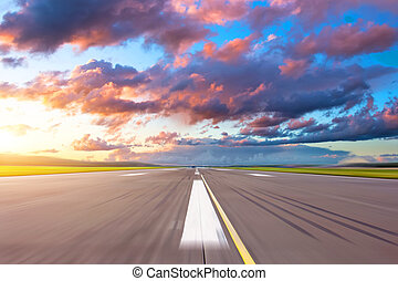 Runway at the airport in the evening sunset sun light bright red clouds.