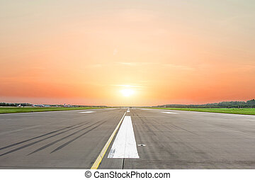Runway at the airport in the evening sunset sun light.