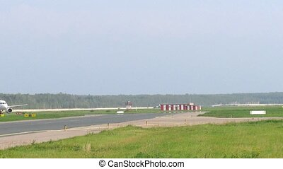 Runway is shown, green grass nearby lies, plane goes on runway