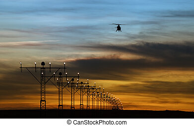 runway lights and silhouette of a helicopter againts summer...