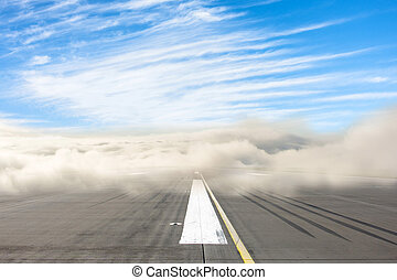 Runway road wrapped in dense low fog, clear blue sky from above. The concept of bad weather at the airport, the delay in the schedule of transport.