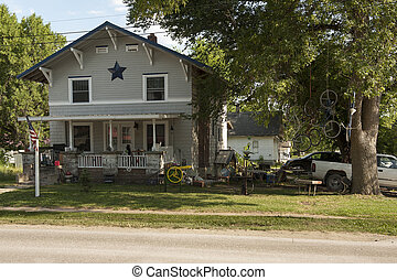 The yard of a rural home displays pure Americana style with an amazing variety of clutter from the beer cans, guitar cases and grill on the porch to the bicycles dangling from ropes in the tree.