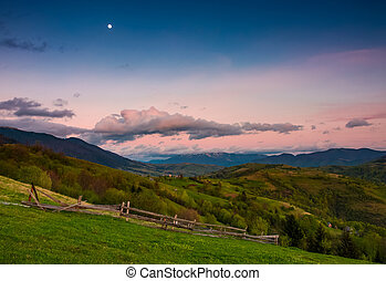 rural area at dusk with moon on cloudy sky