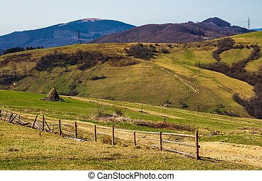 rural area on rolling hills in springtime. wooden fence and...