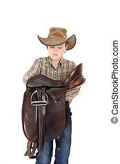 Rural boy holding a saddle