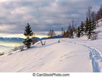 rural footpath through snowy hillside. beautiful scenery of...