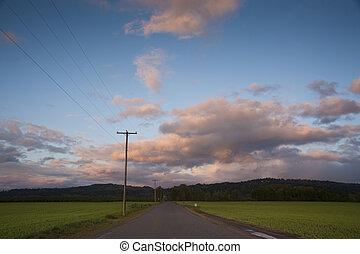 Rural highway under sunset clouds