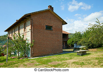 Rural house in red bricks in a sunny summer day, Italy