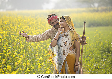 Rural indian couple standing in rapeseed field