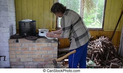 rural kitchen furnace - grandmother boil a pot on old brick...