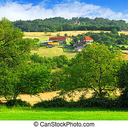 Scenic view on summer agricultural landscape in rural France with a farmhouse and barn