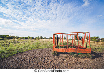 Rural landscape with a cage on a field