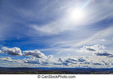 Rural landscape with blue sky and clouds.
