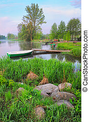 Rural landscape with boat and footbridge on the Narew river after fog, Poland.
