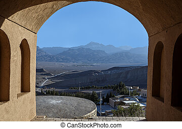 Rural landscape with mountains behind the archway, near Yazd, Iran.
