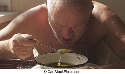 Rustic aged man eating a soup with meat