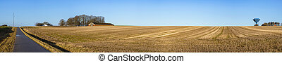 Rural panorama landscape with a dry field