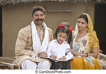 Rural parents helping daughter to do school homework