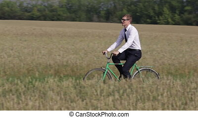 Rural rider - Young entrepreneur riding a bike across the...
