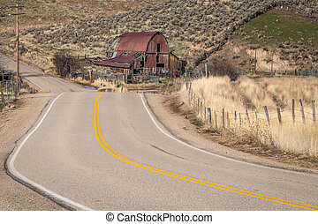 Rural road and rusted old barn in the country