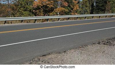 Rural road. Cars passing.