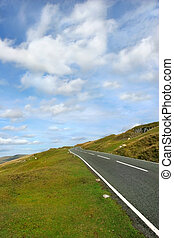 Rural Road - Steep uphill road with grass verges on either ...