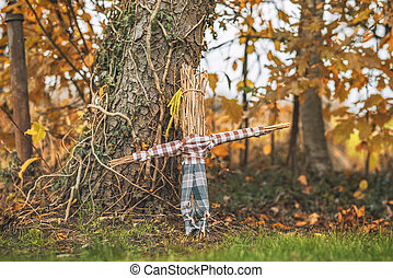 Rural scarecrow standing in a garden in the autumn with shirt and pants